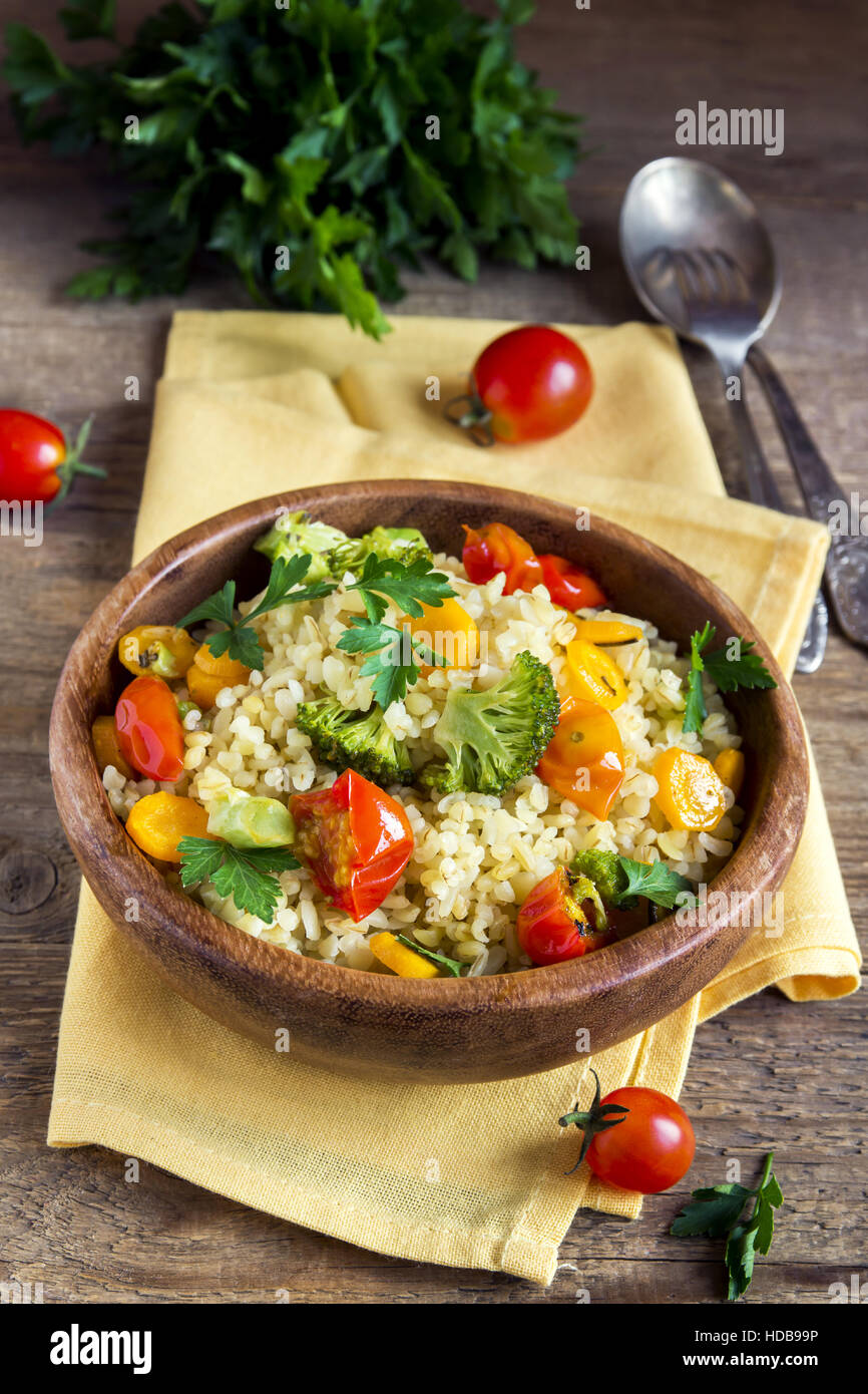 Delicious homemade vegetarian bulgur (couscous) with vegetables: tomatoes, carrots, zucchini, broccoli and parsley - Stock Image