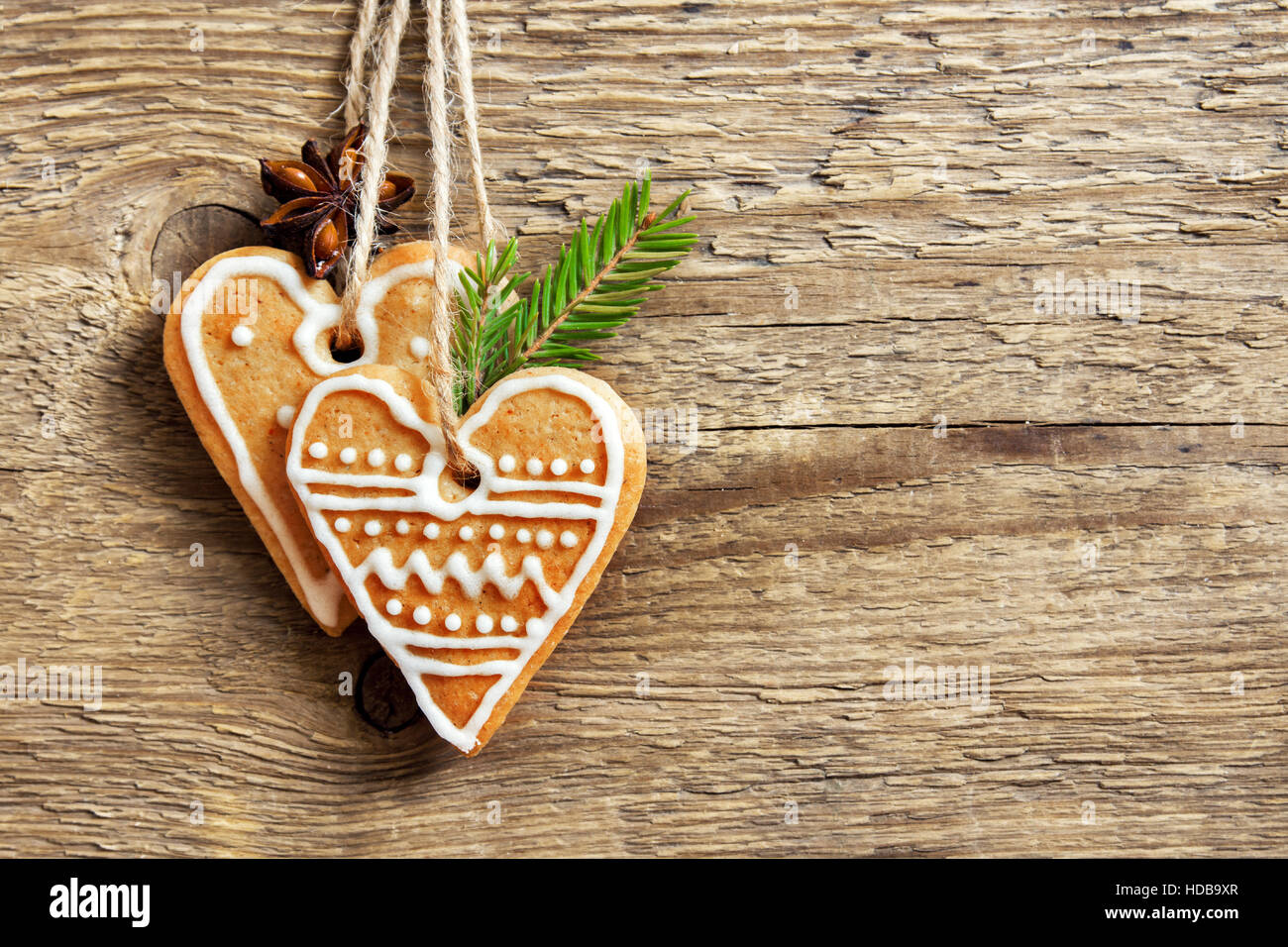 Christmas wooden background with gingerbread cookies heart shape, copy space - homemade festive decor, greeting - Stock Image