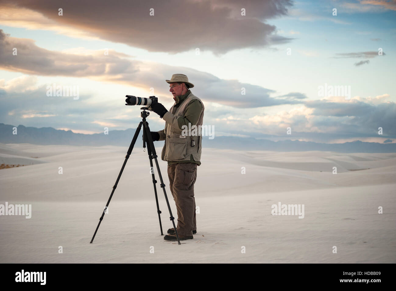 An amateur photographer taking photos / chimping at the back screen of his camera at White Sands National Monument, - Stock Image