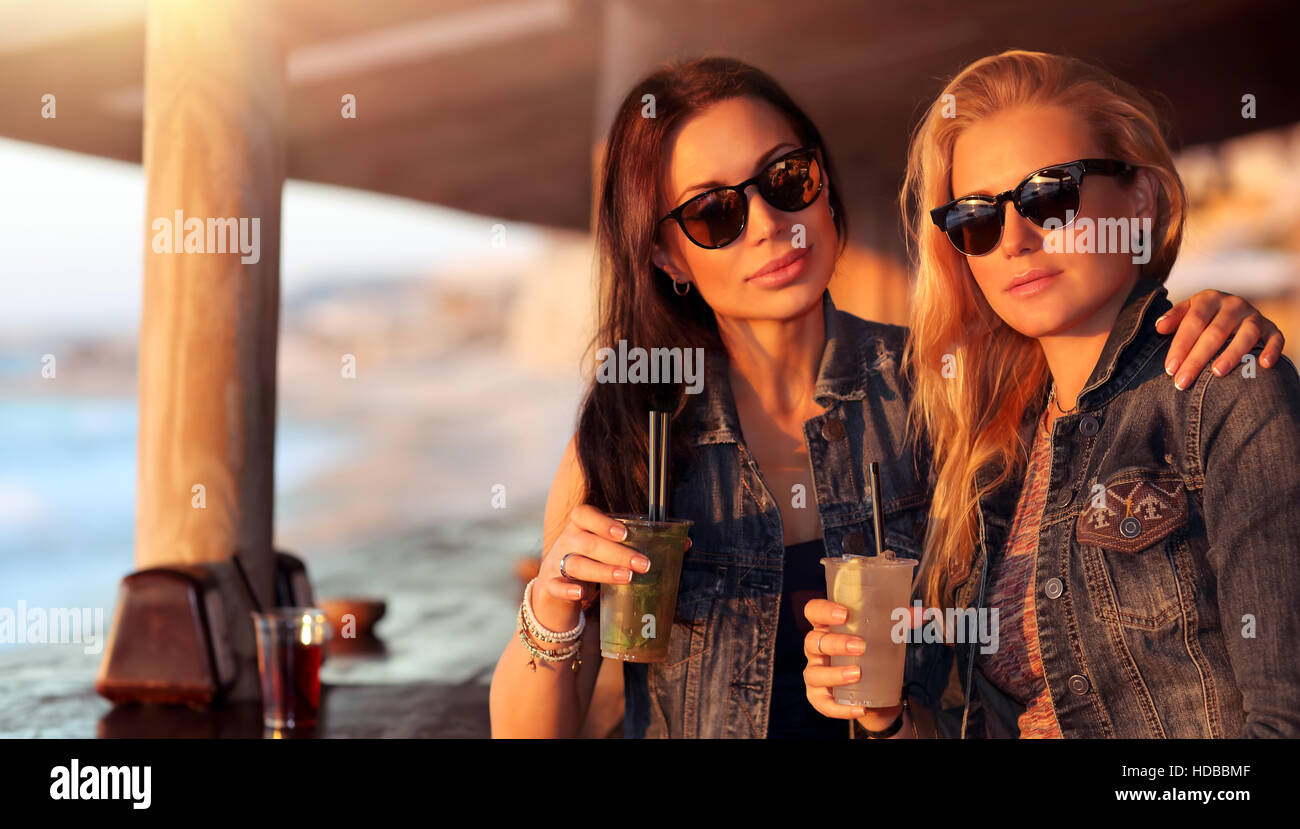 Portrait of a two beautiful girls spending leisure time in the outdoor cafe with drinks, models wearing stylish - Stock Image