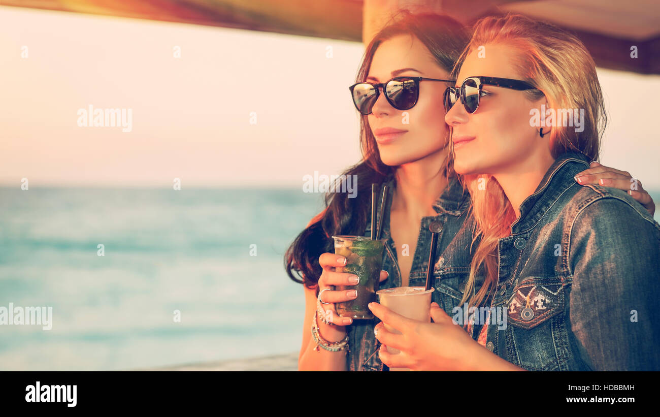 Portrait of a two beautiful girls spending leisure time in the outdoor cafe, drinking tasty cocktails and enjoying - Stock Image