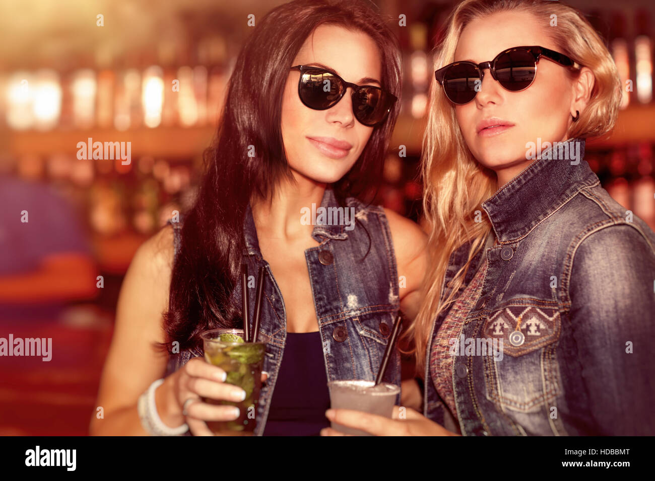 Two gorgeous women with refreshing drinks having fun in the outdoor bar, wearing stylish sunglasses and enjoying - Stock Image