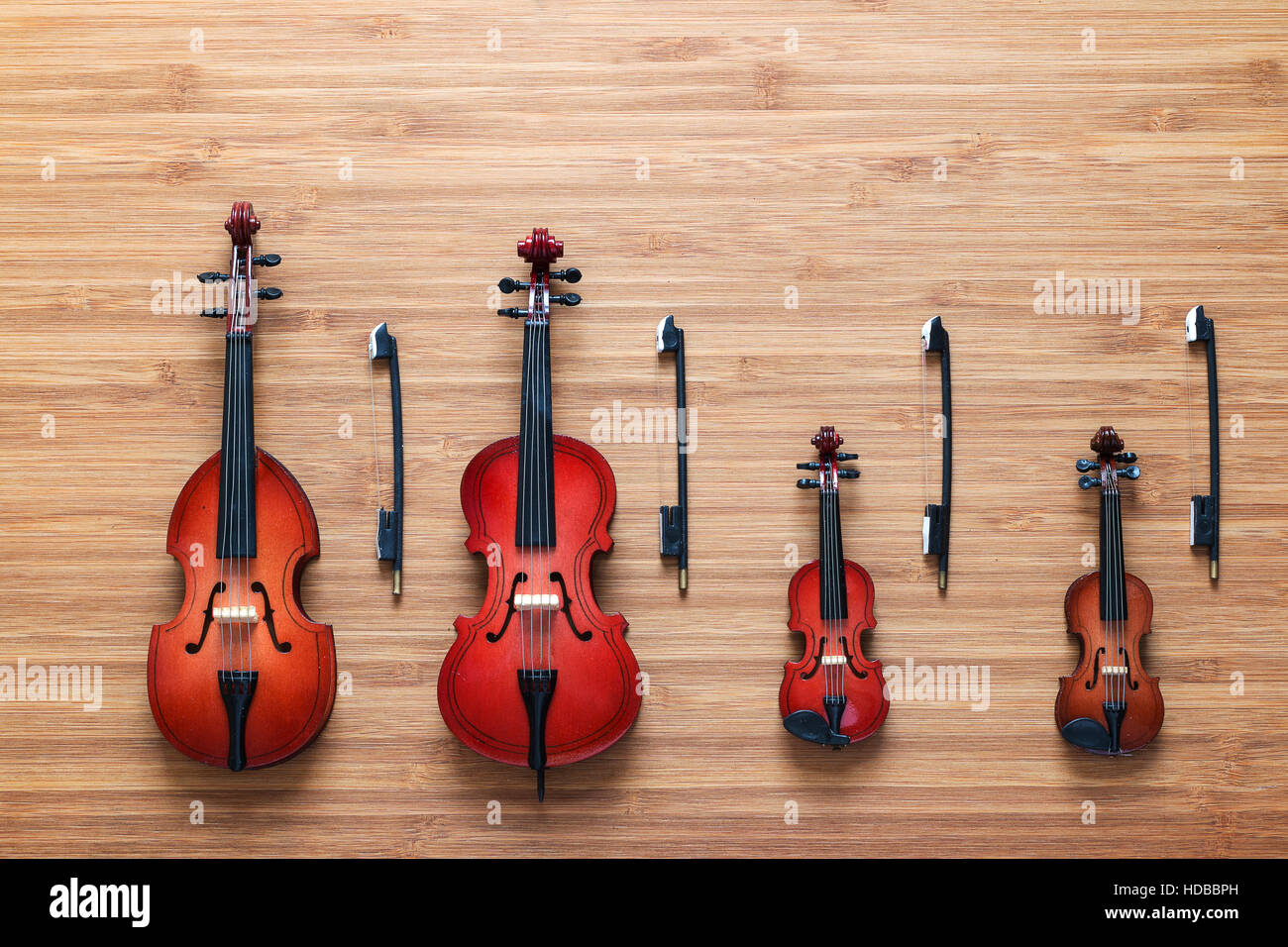 Set of four toy string musical orchestra instruments: violin, cello, contrabass, viola on a wooden background. Quartet. Music concept. Stock Photo