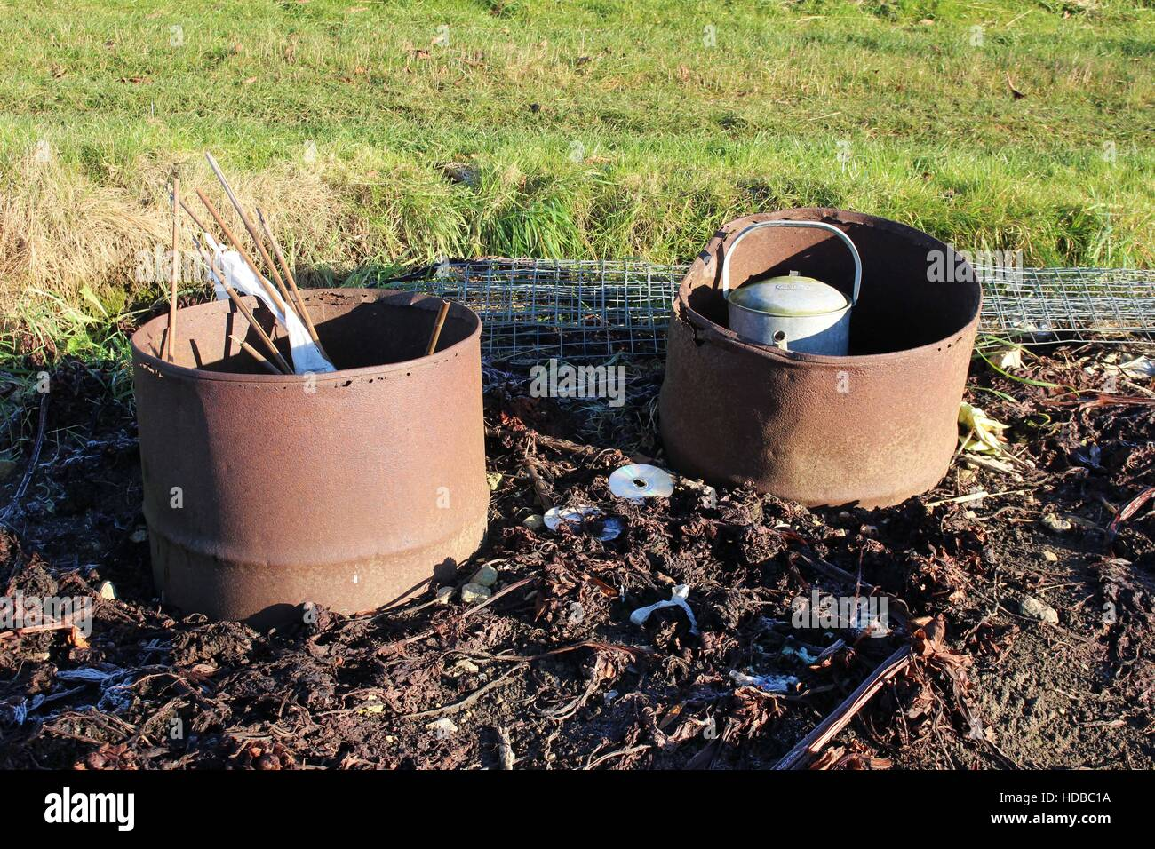 Winter allotment rusty metal barrels wire watering can cane bamboo canes mess messy gardening - Stock Image