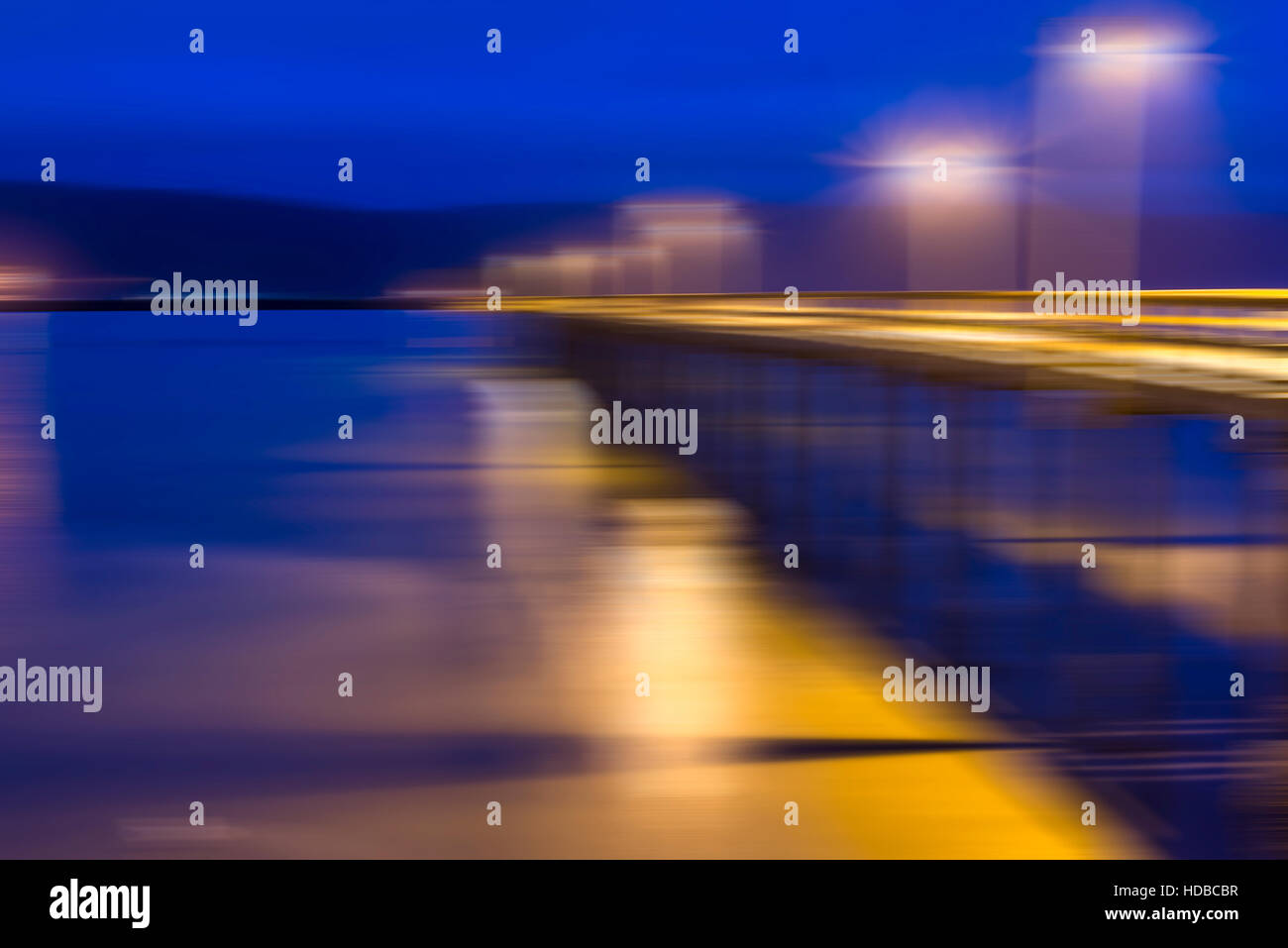 motion blur effect, pier with lamppost at night. - Stock Image