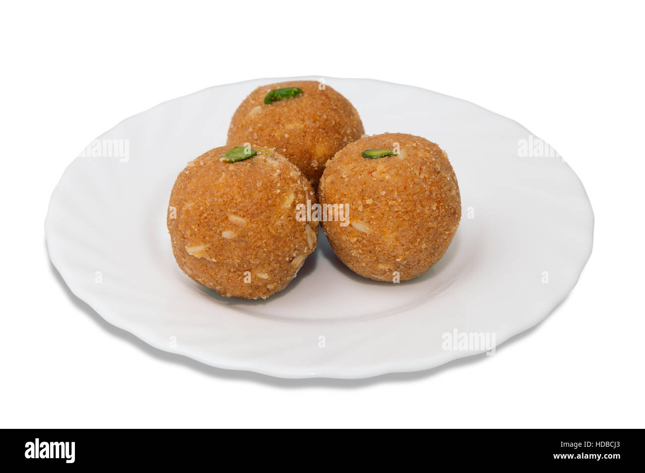 Indian sweets on a plate isolated over white - Stock Image