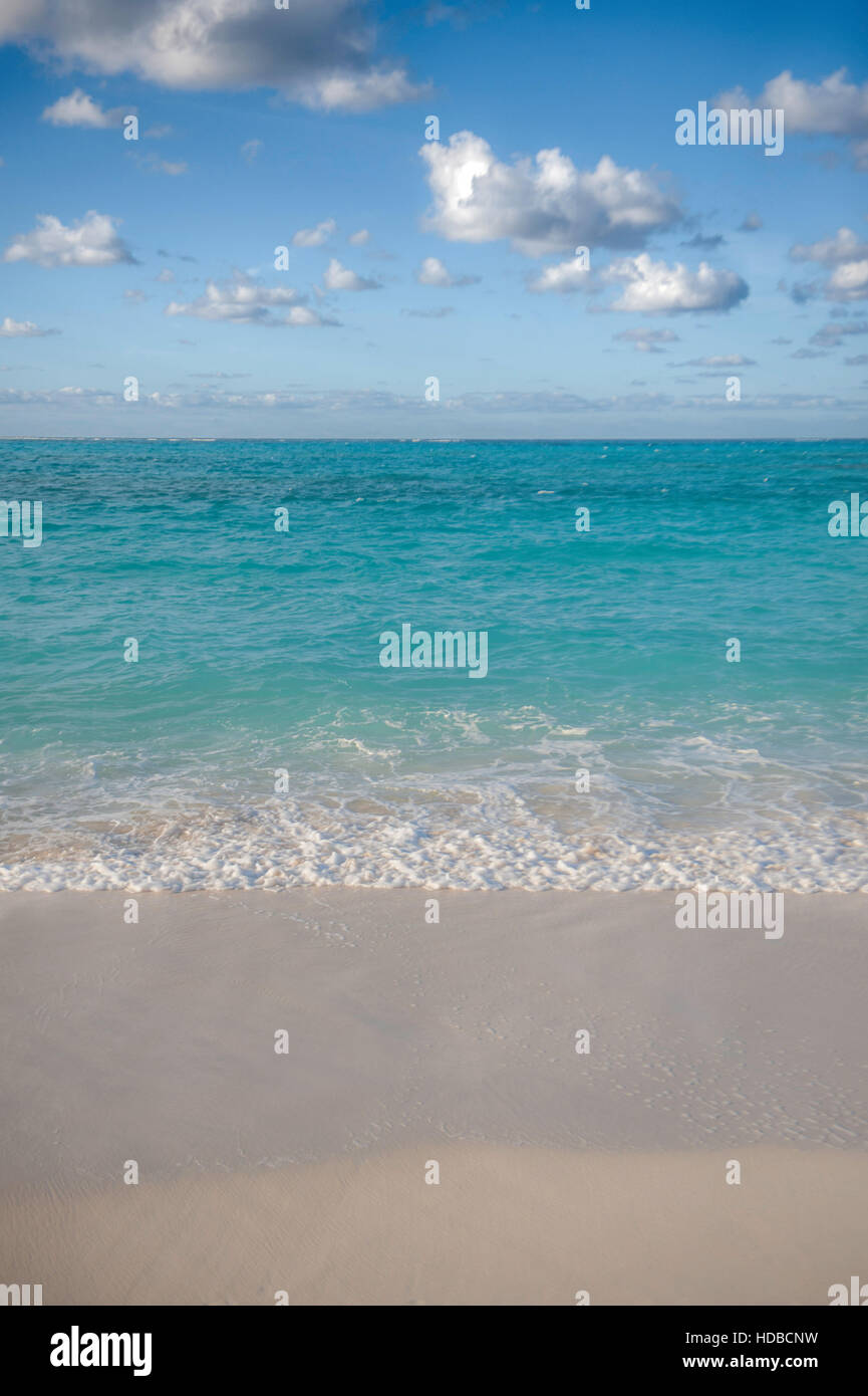 The blue sky, turquoise sea and golden sand of Turks & Caicos. Clouds, surf and beach are perfectly divided - Stock Image