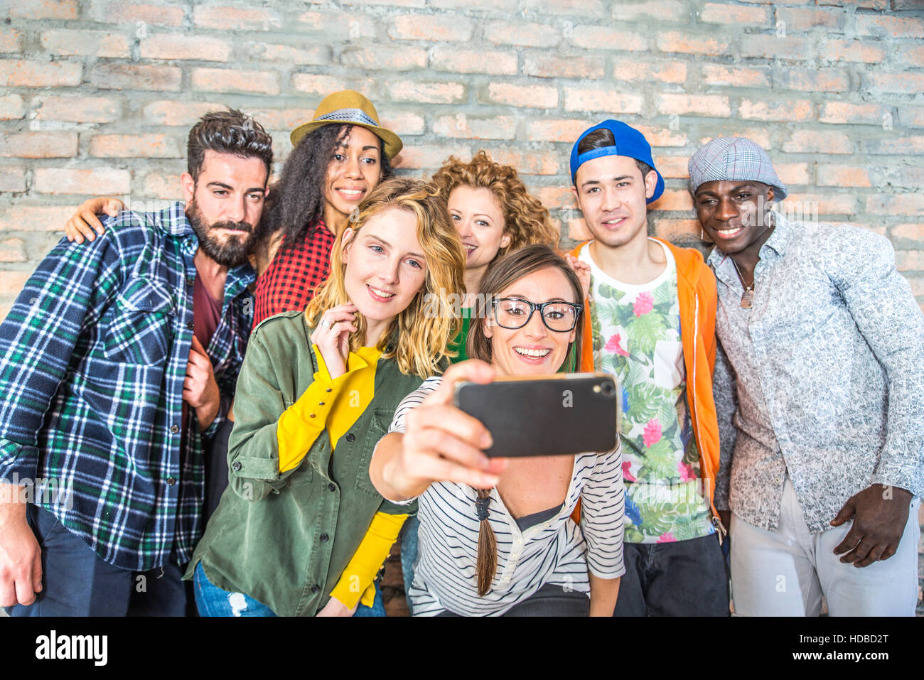 Group of people with coloroful trendy clothes bonding together and having fun - Young cheerful friends taking a - Stock Image