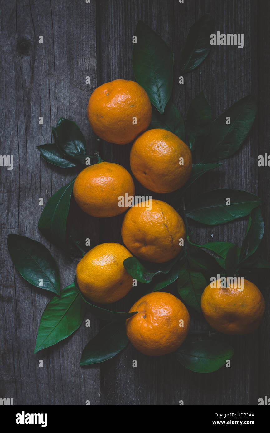 Fresh tangerines with green leaves on rustic wooden table. Top view, vertical composition, toned image. - Stock Image