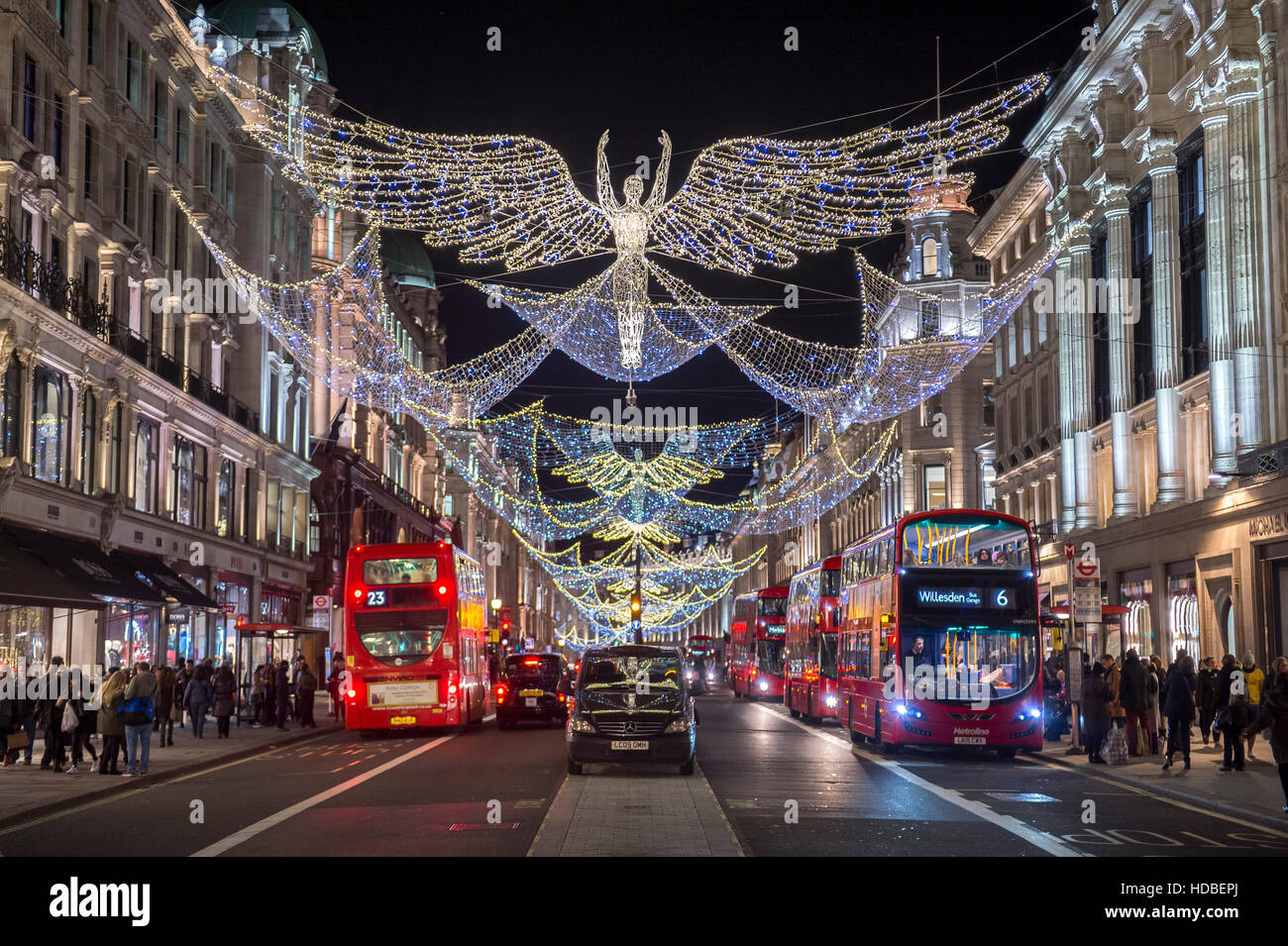 LONDON - NOVEMBER 18, 2016: Traditional black taxi awaits customers under twinkling Christmas angels lighting up - Stock Image