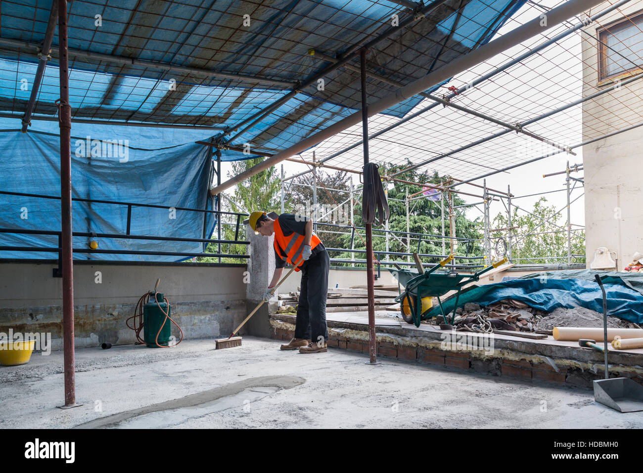 Roofer is cleaning the bottom of a terrace before the laying of bituminous waterproofing membrane rolls - Stock Image