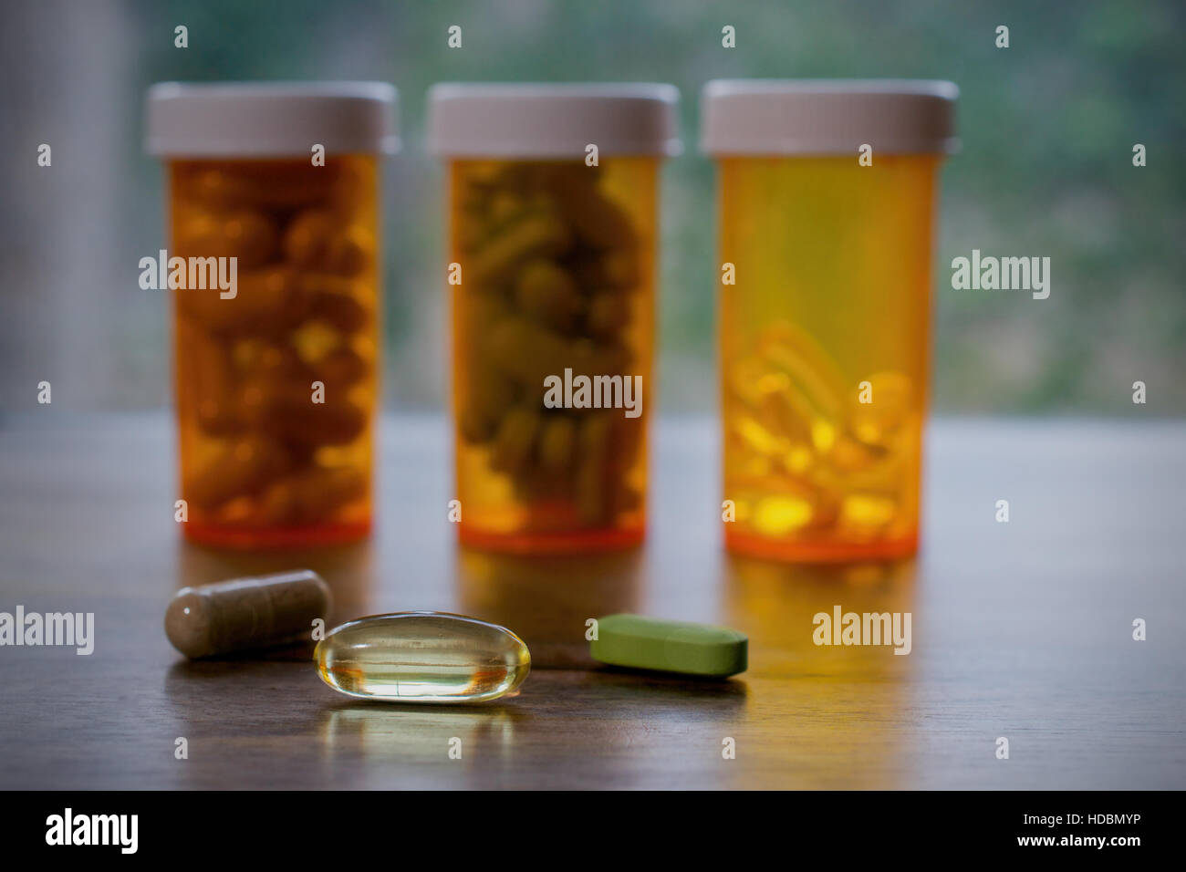 Dietary supplements in yellow bottles on a windowsill - Stock Image