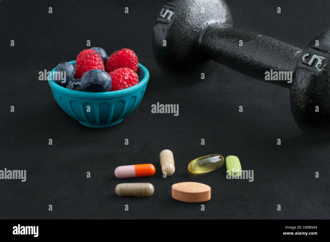 Dumbbell, berries and dietary supplements on black background: Fitness and weight loss concept. - Stock Image