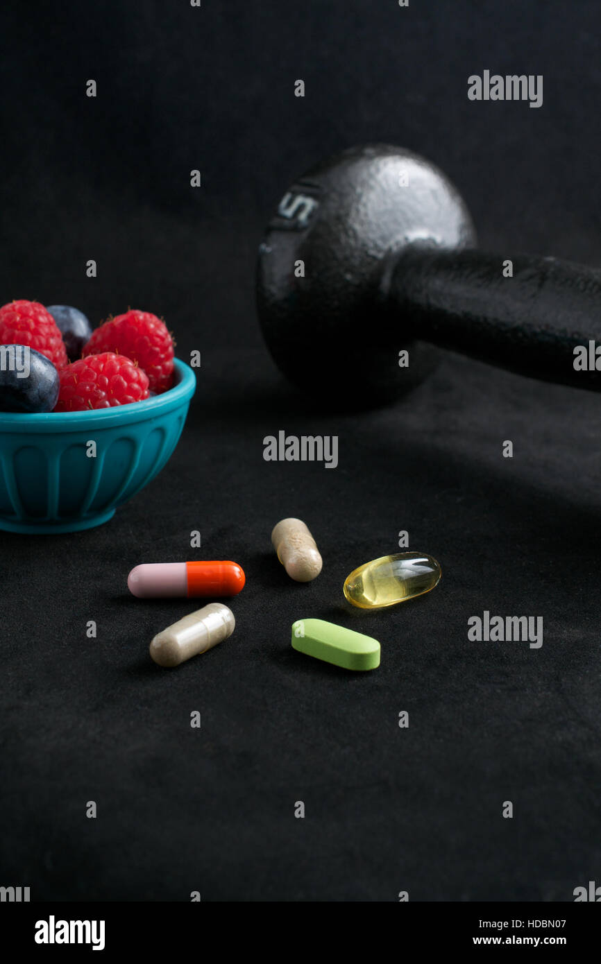 Dumbbell, berries and dietary supplements on black background.Fitness and weight loss concept. - Stock Image