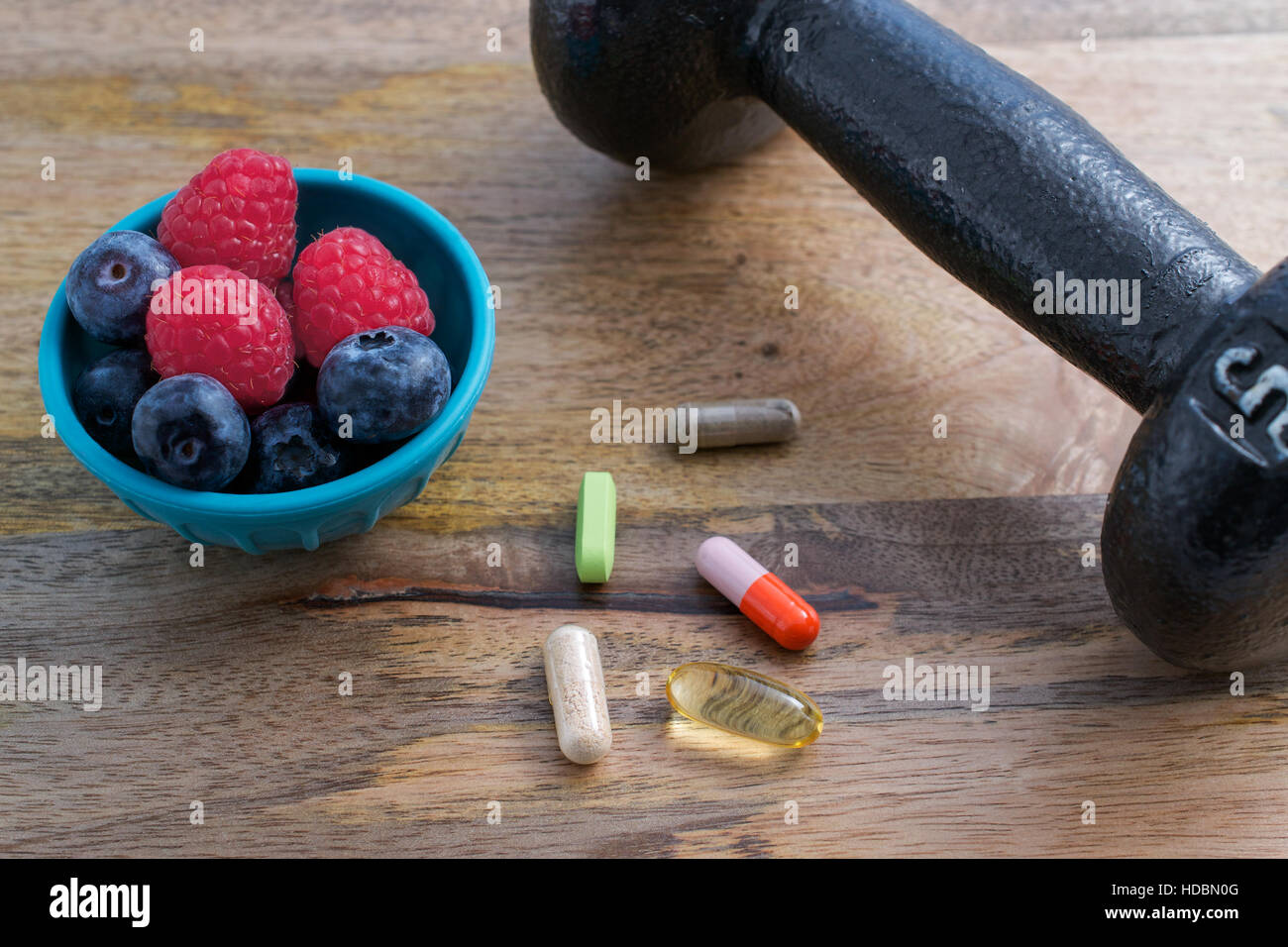 Dumbbell, berries and dietary supplements on wooden background: Fitness and weight loss concept. - Stock Image