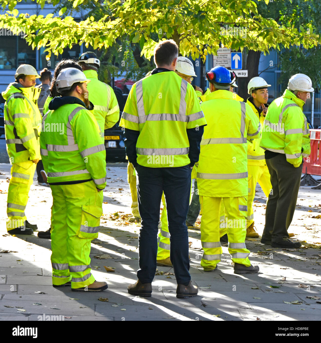 Group of people hard hat men man standing around informal team meeting near major road works project London England - Stock Image