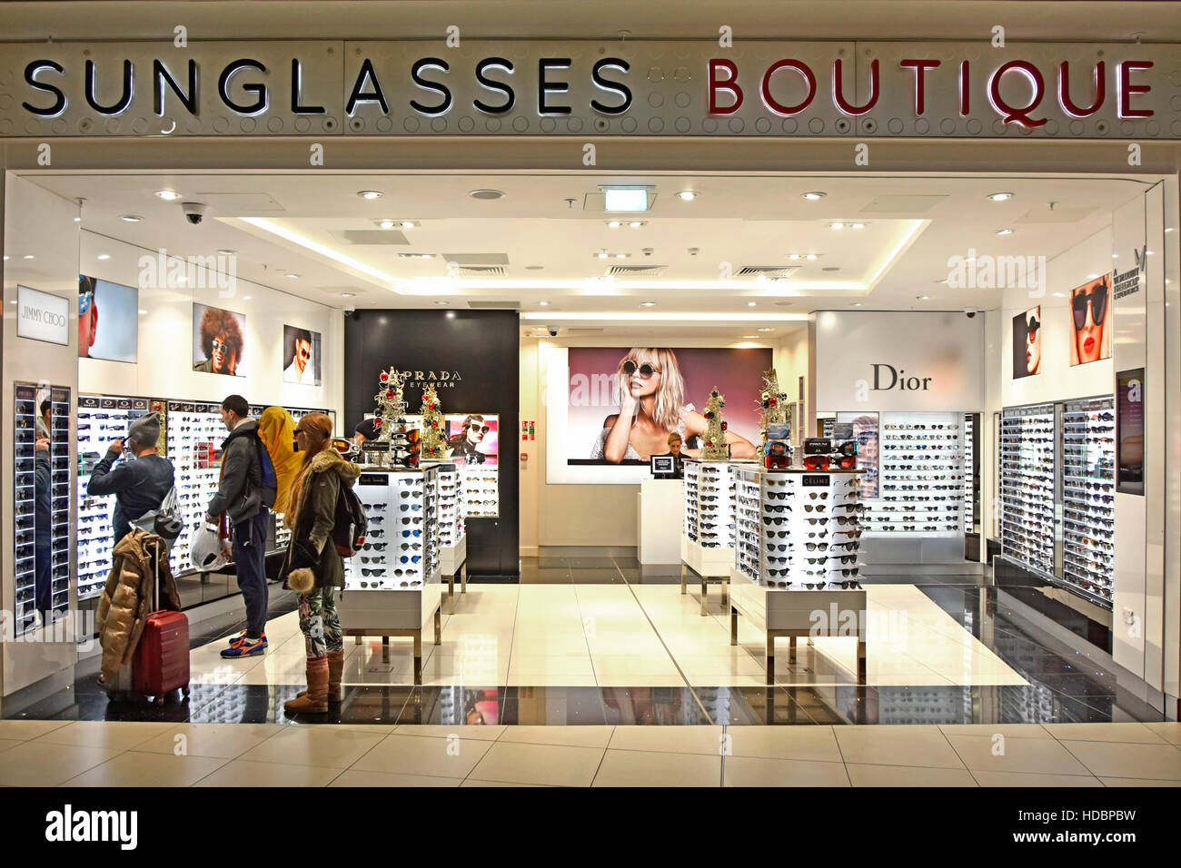 0a8312ee7b15 Stansted Airport London travellers shopping Sunglasses Boutique adjacent to  departure lounges interior of airport - Stock