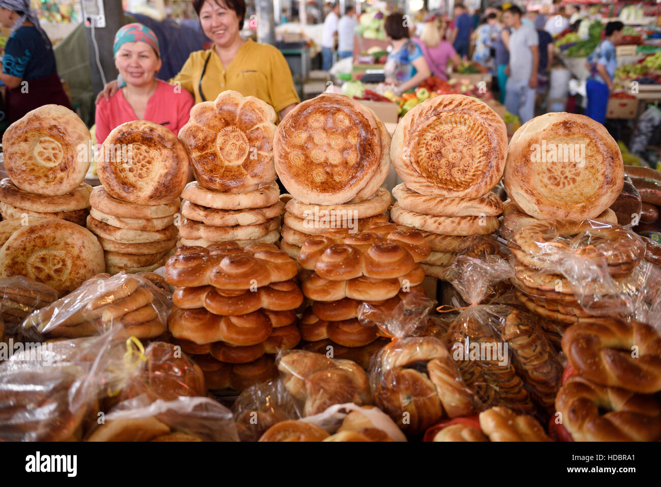 Shop keepers in Shymkent Central Market next to table of Kazkh Tandyr nan breads Kazakhstan Stock Photo