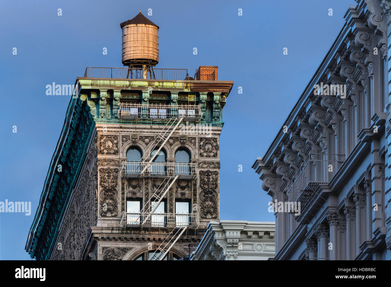 Soho building with terra cotta ornamentation, cornice, fire escape and water tower lit by sunset light. New York - Stock Image
