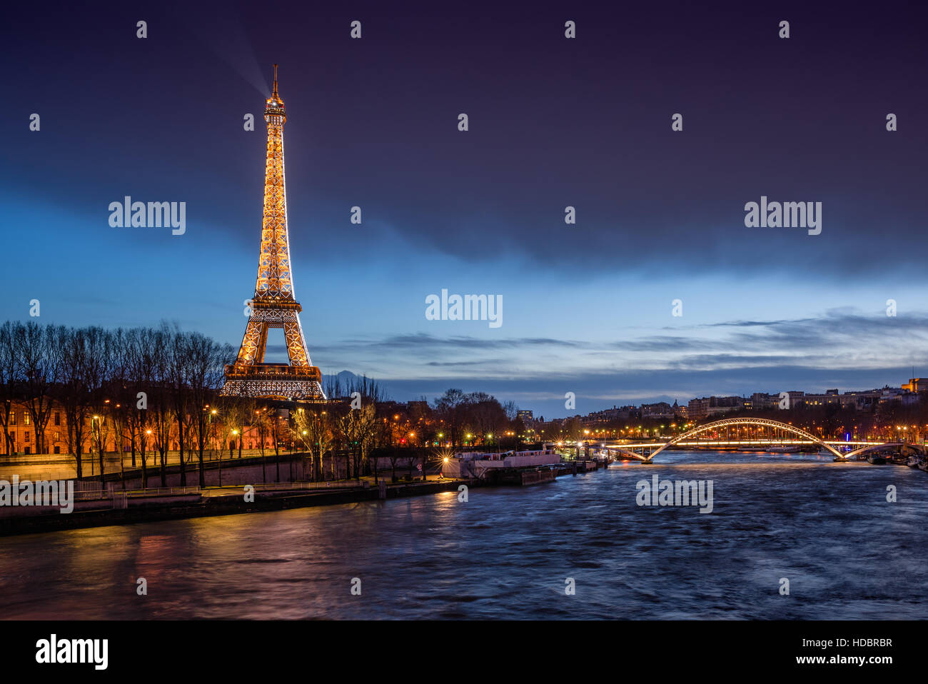 The Eiffel Tower illuminated at twilight with banks of the Seine River and the Debilly Footbridge. Paris, France - Stock Image