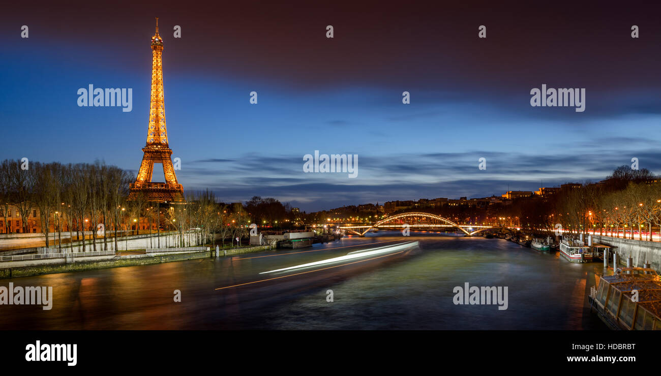 The Eiffel Tower illuminated at twilight with the Seine River banks and the Debilly Footbridge. Paris, France - Stock Image