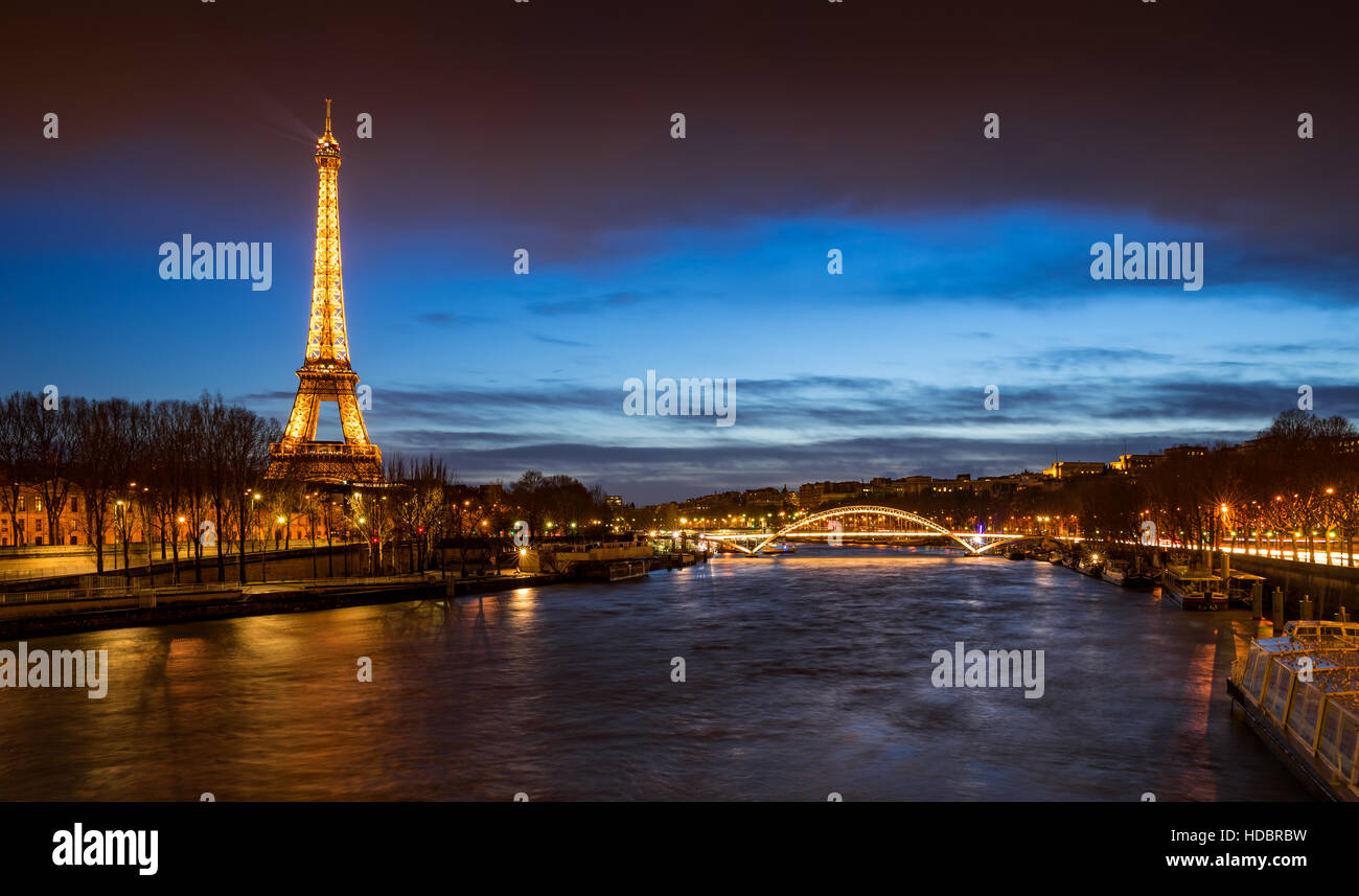 The Eiffel Tower illuminated at twilight with the Seine River banks and the Debilly Footbridge. Paris, France Stock Photo