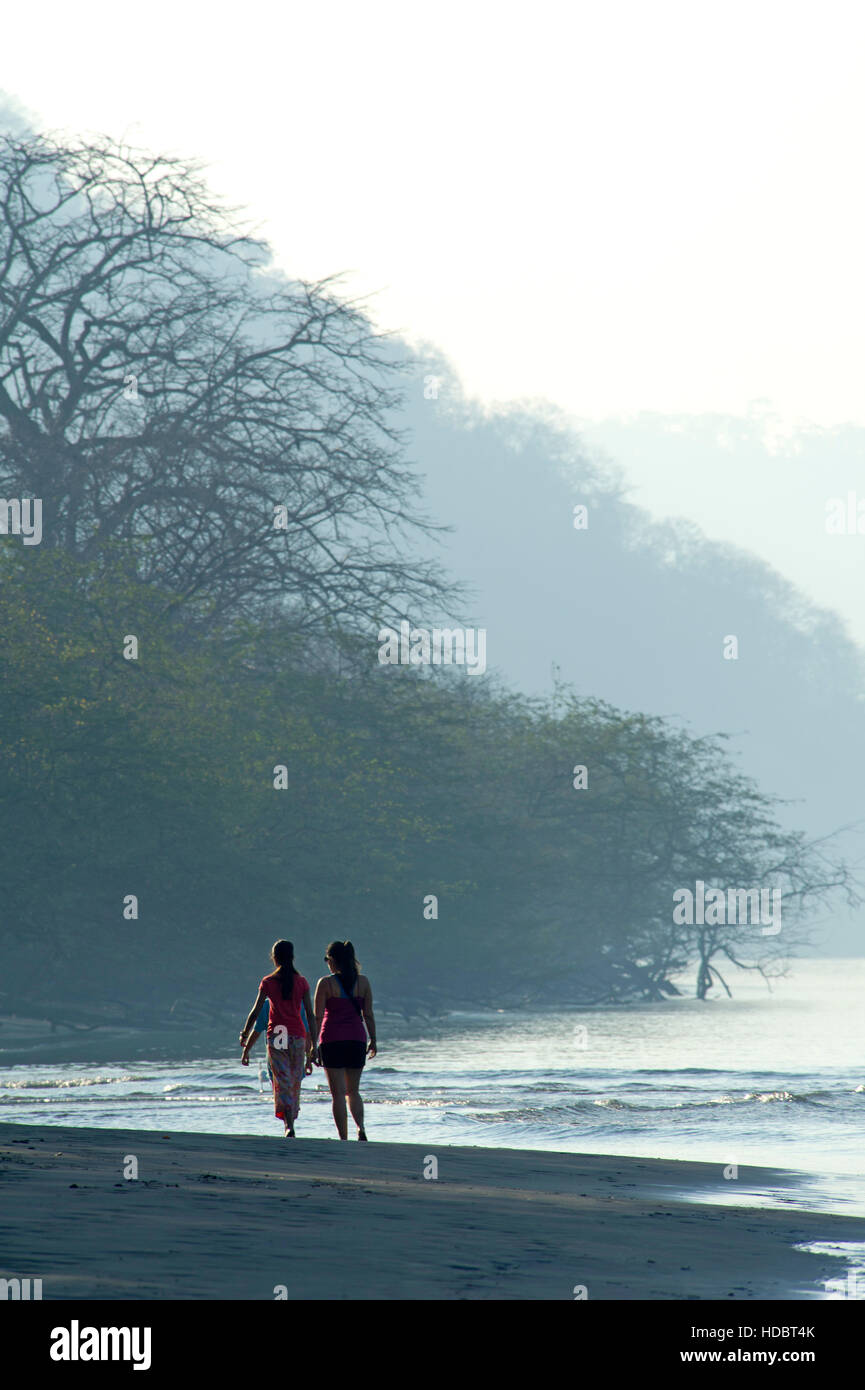 Tourists walking on a beach in the evening haze in Costa Rica - Stock Image
