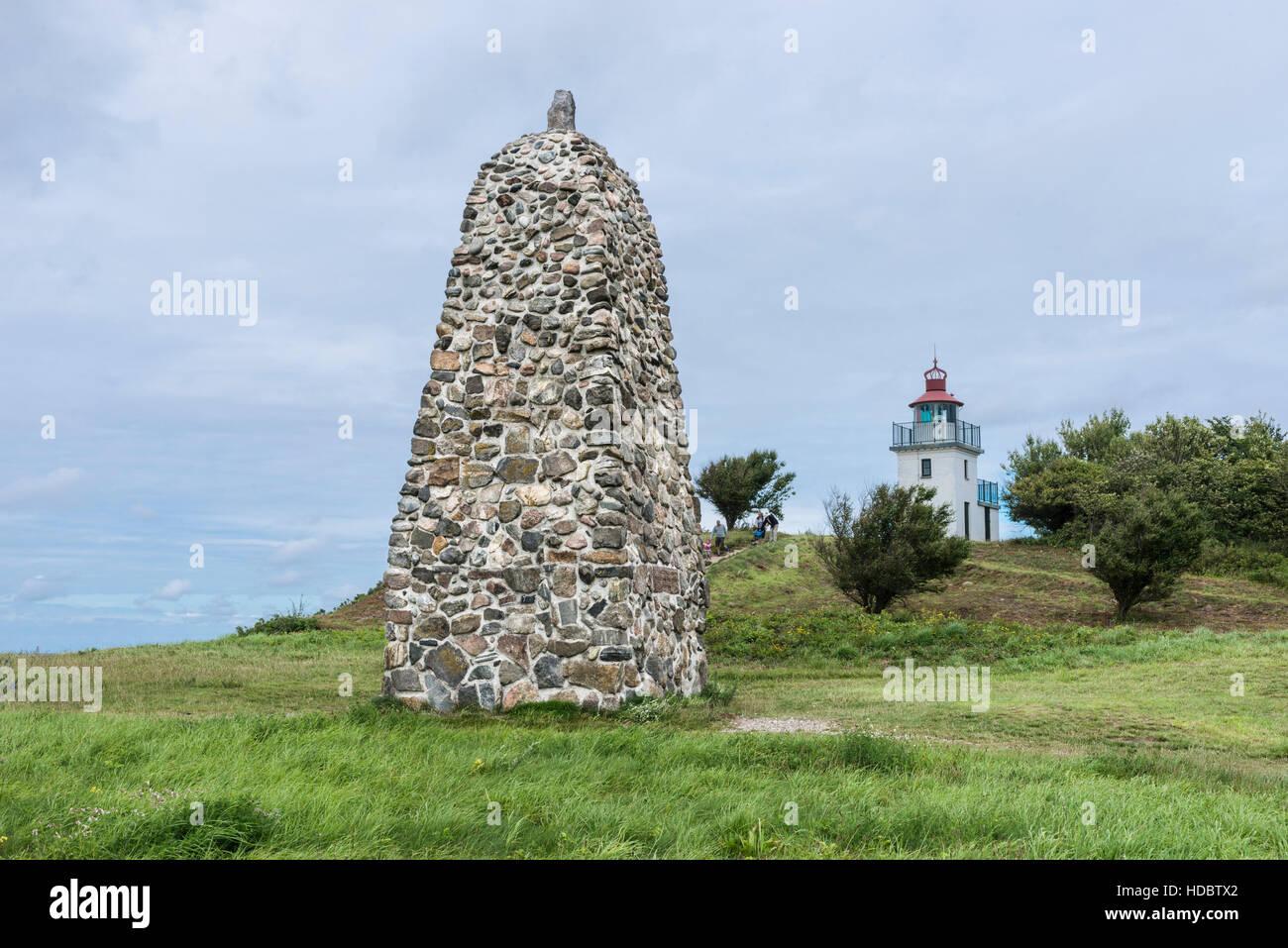 Memorial stone for polar explorer Knud Rasmussen, lighthouse behind, Hundested, Capital Region of Denmark, Denmark - Stock Image