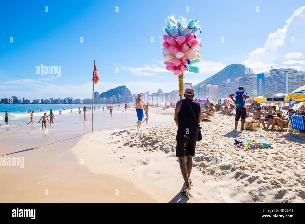 RIO DE JANEIRO - FEBRUARY 27, 2016: Brazilian beach vendor selling cotton candy floss approaches customers on Copacabana. - Stock Image