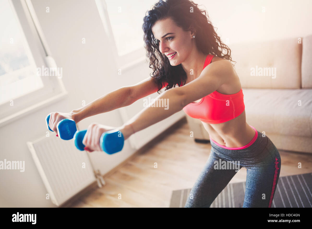 Fit sportswoman exercising and training at home - Stock Image