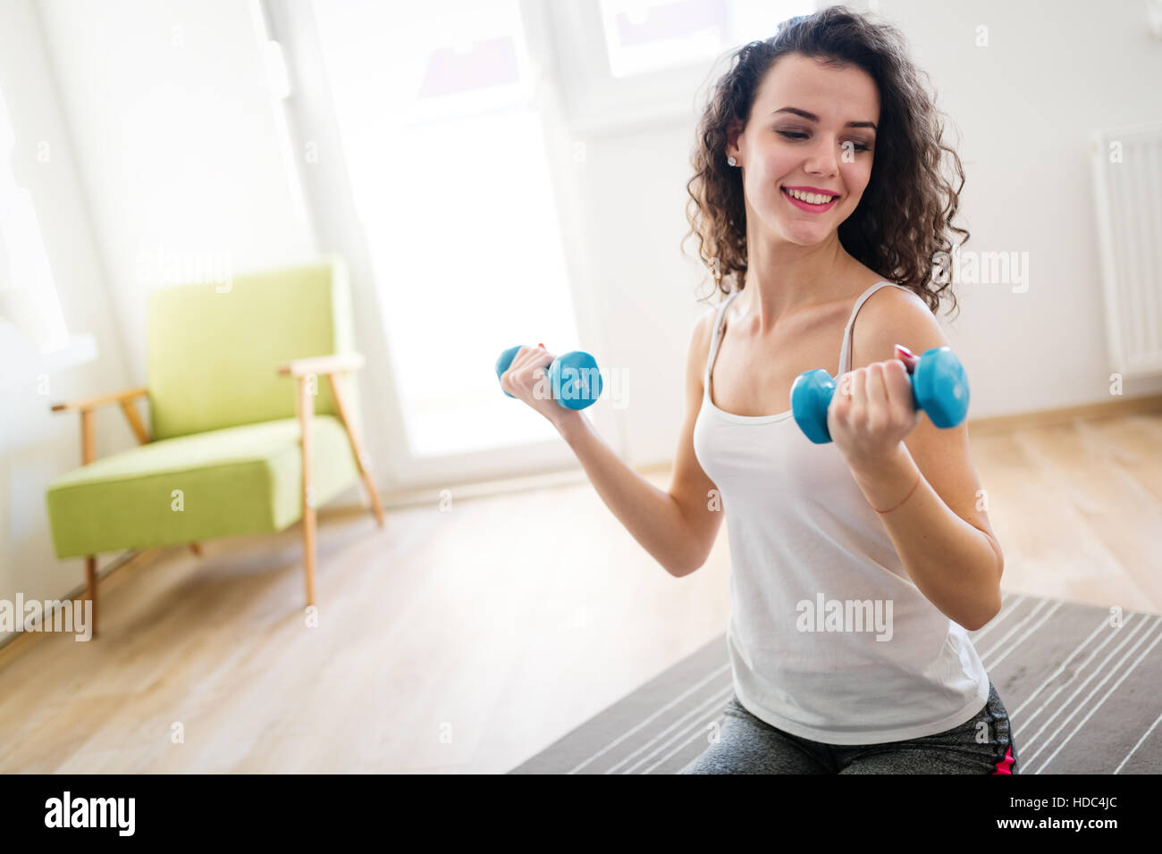 Sporty beautiful woman exercising at home to stay fit - Stock Image
