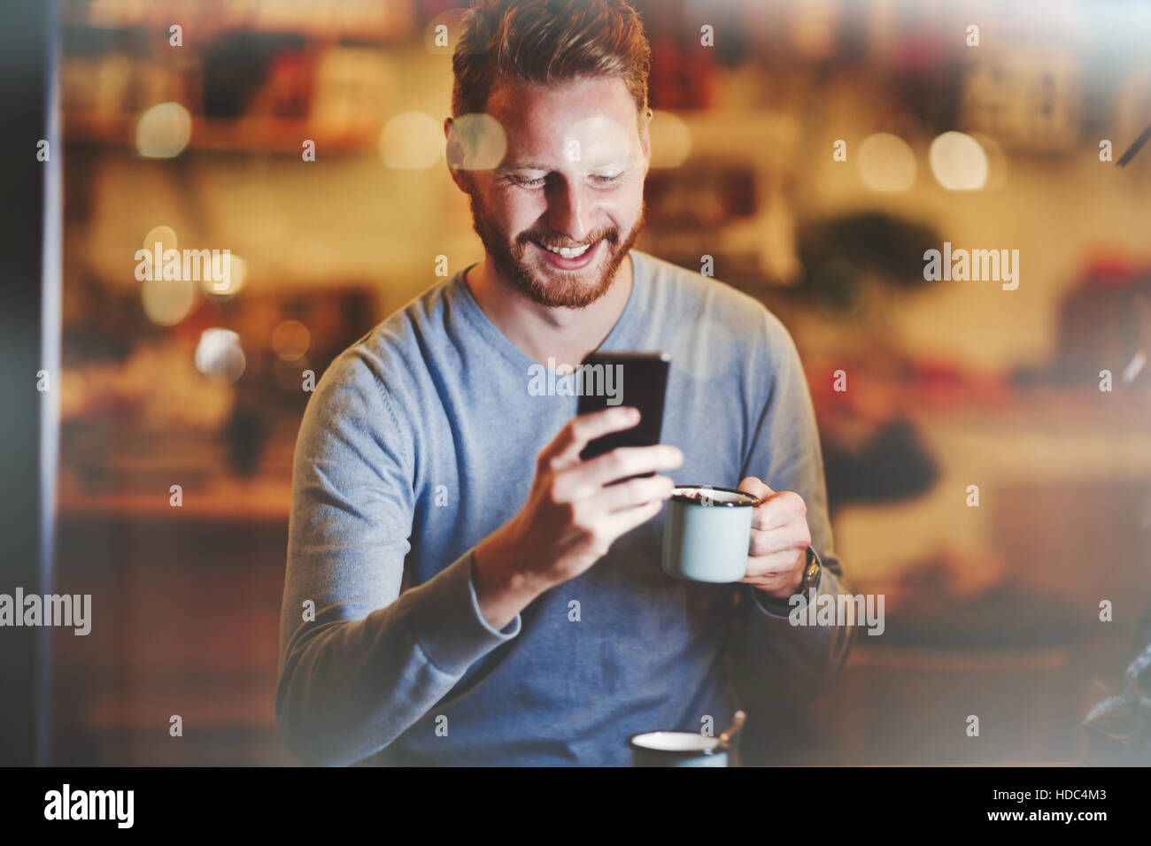Cheerful businessman drinking coffee in cafe - Stock Image