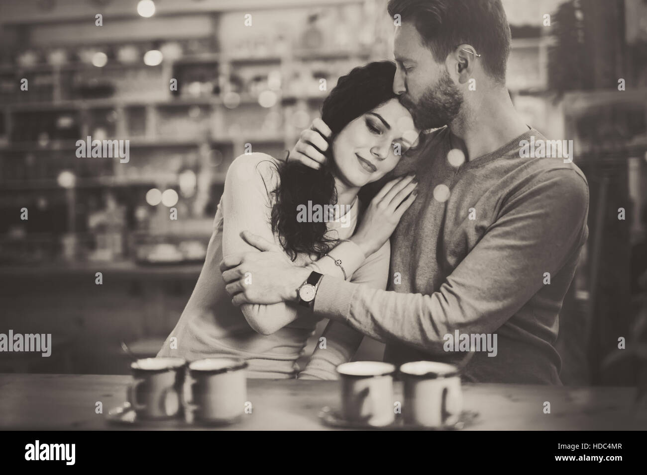 Handsome male kissing woman on forehead in cafe - Stock Image