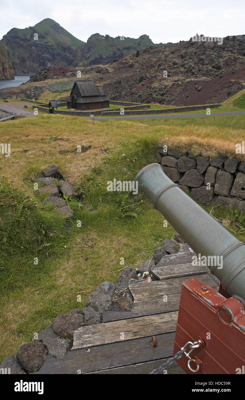 Old gun, Norwegian Stave Kirke and edge of the lava field caused by the eruption of Eldfell in 1973, Heimaey, southern - Stock Image