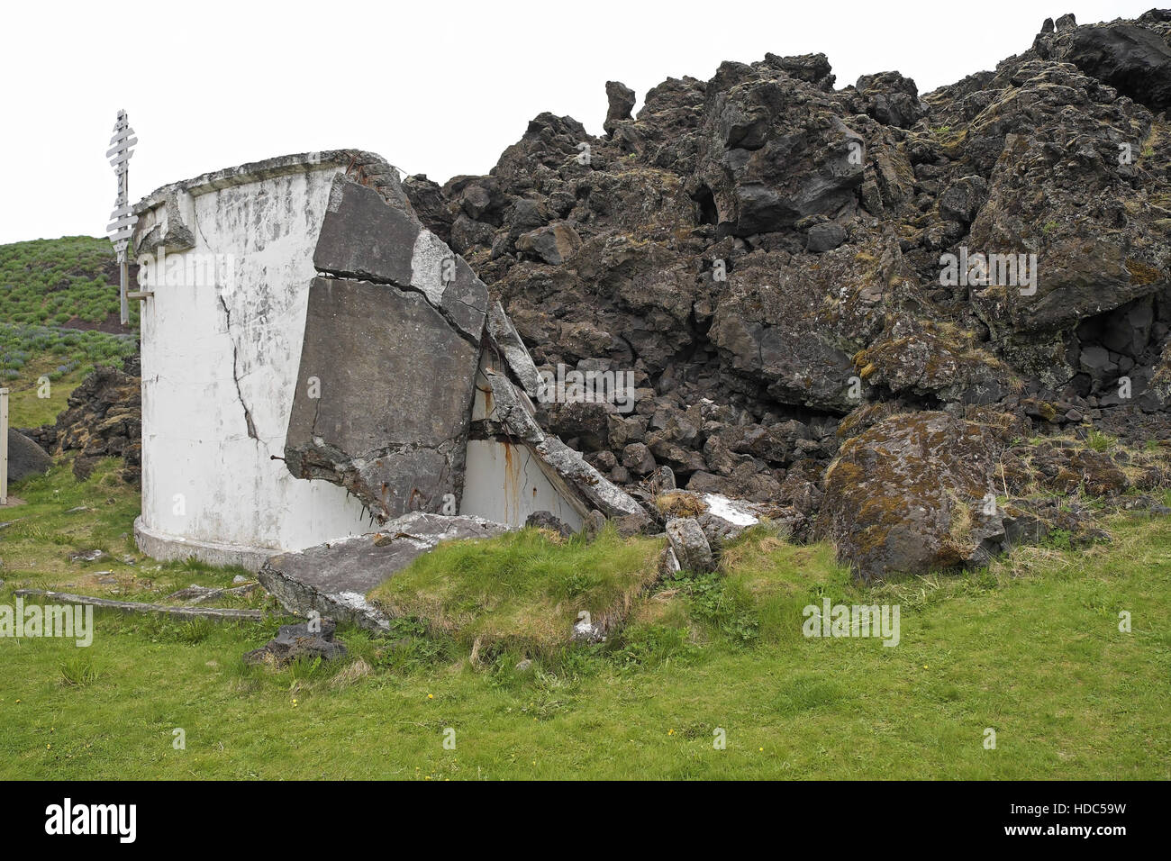 Edge of the lava field and destroyed concrete tank caused by the eruption of Eldfell in 1973, Heimaey, Iceland. - Stock Image