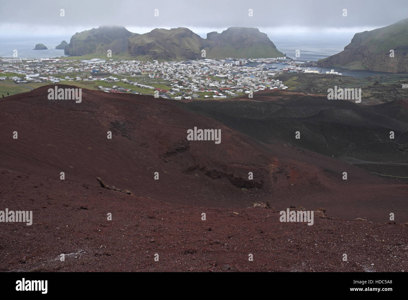Heimaey seen over volcanic rocks and lava field from of Eldfell, Heimaey, Vestmannaeyjar Islands, southern Iceland - Stock Image