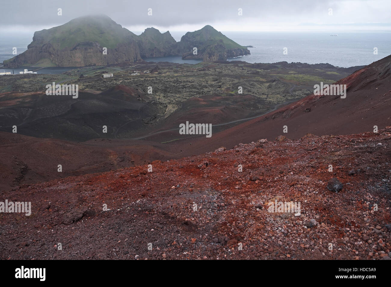 Town of Heimaey seen over volcanic rocks and lava field from Eldfell, Heimaey, Vestmannaeyjar Islands, southern - Stock Image
