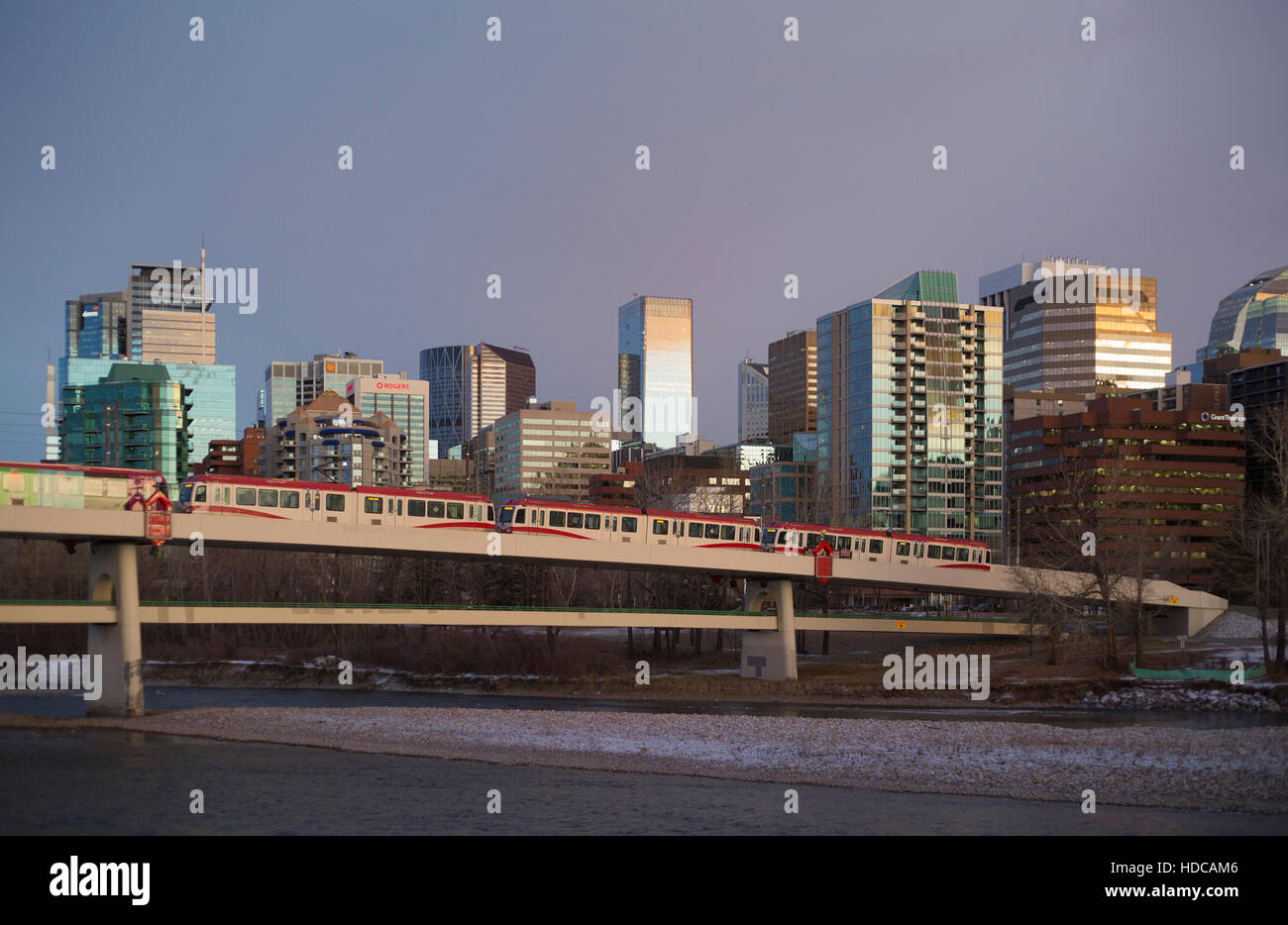 Light rail electric train powered by wind energy crossing Bow River to downtown Calgary, pedestrian bridge underneath - Stock Image