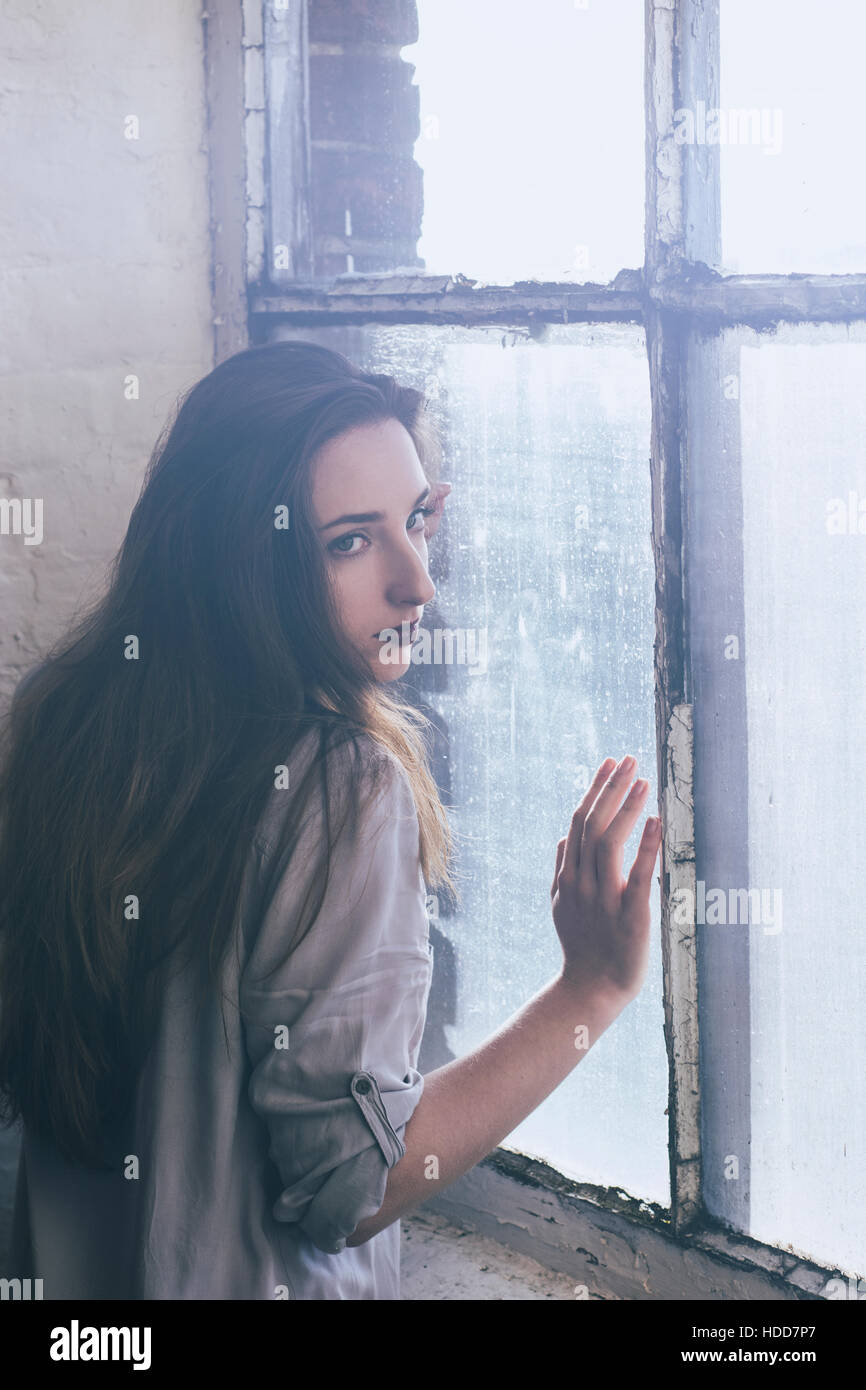 Sad woman leaning on the window - Stock Image