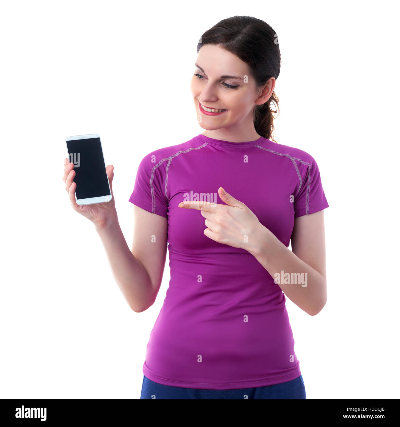 Smiling sporty woman in violet T-short showing something on smart phone device over white isolated background, fitness, - Stock Image