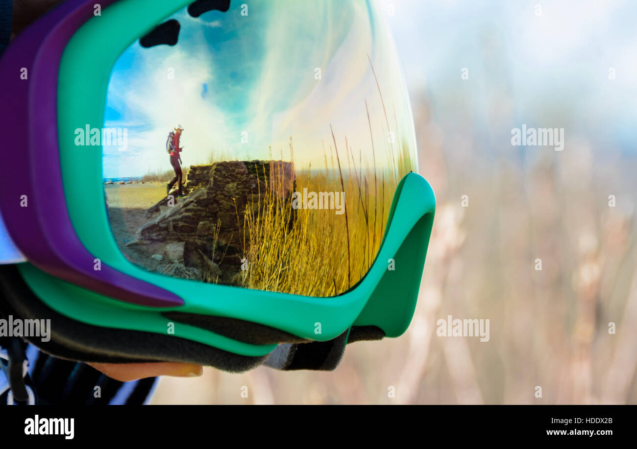 Ski goggles with reflection of backpacker at summit - Stock Image