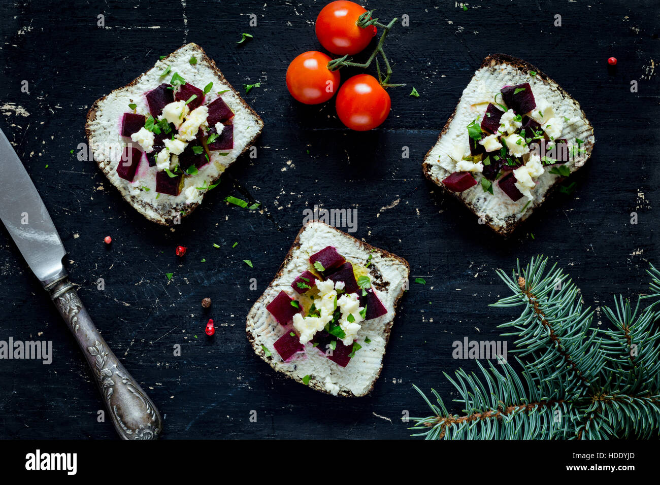 Christmas appetizers with roasted beet and goat cheese on black board. Top view, close up - Stock Image