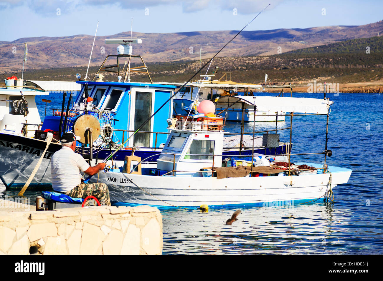 Fishing on the quayside of Agios Georgios harbour, Paphos, Cyprus. - Stock Image