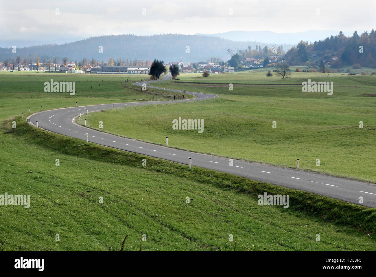 A winding road through grassland and meadows  leads to town of Logatec, Slovenia - Stock Image