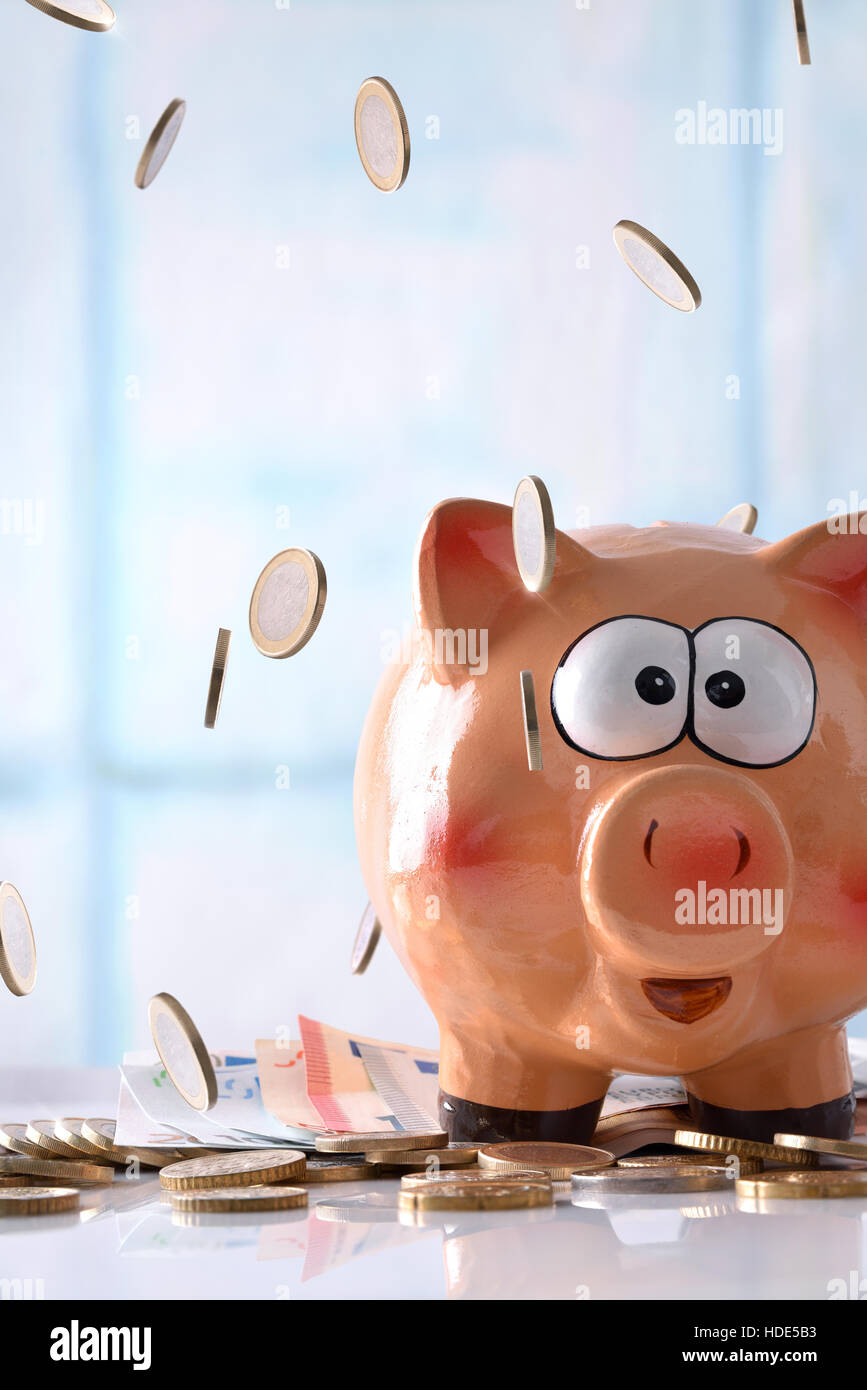 Concept savings with coins falling on piggy bank with savings billboard and stacked coins on reflective white glass - Stock Image