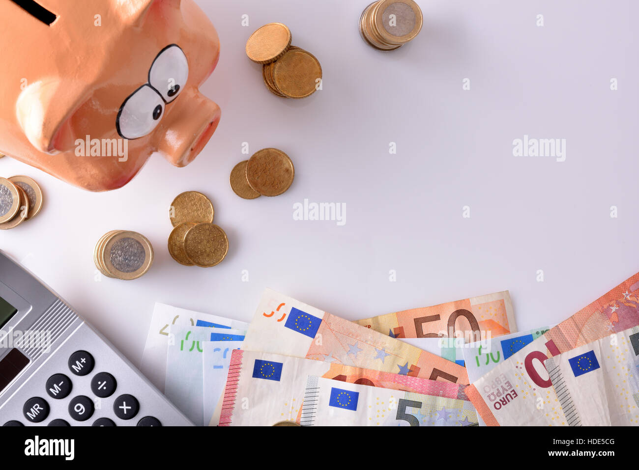 Concept savings and accounting with piggy bank and stacked coins and bills, and calculator on table and white background. - Stock Image