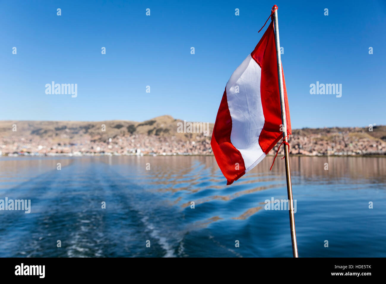 Peruvian flag on tourist boat on Lake Titicaca, City of Puno in background, Puno, Peru - Stock Image