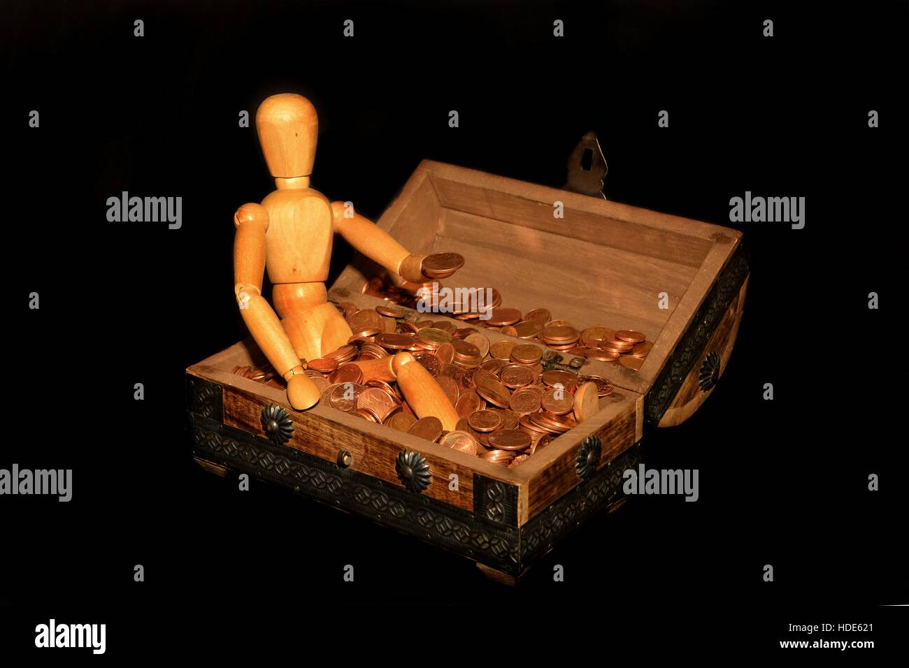 Wooden figure sitting in a wooden box with money, coin on the hand and with dark background - Stock Image