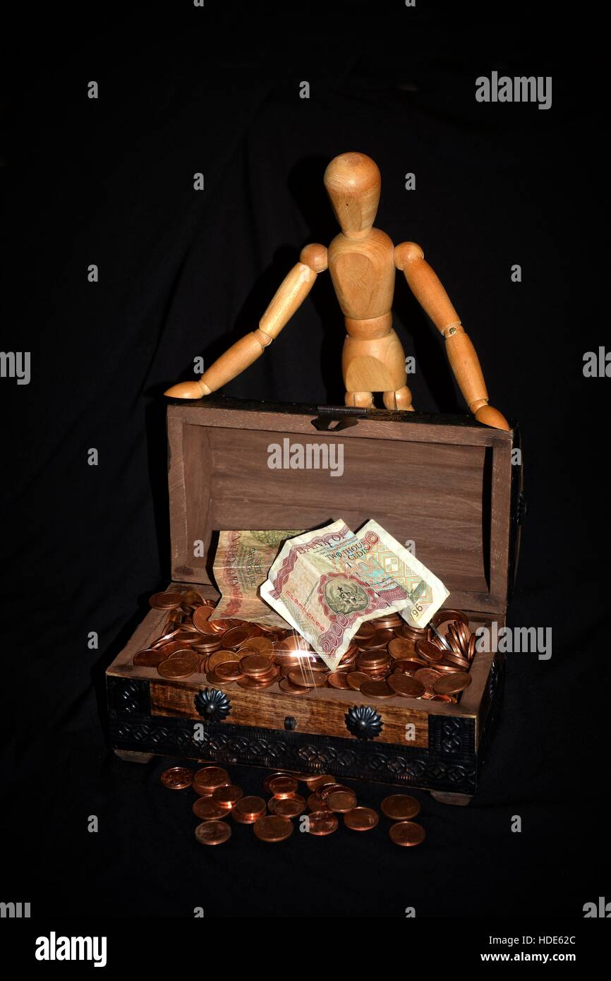 Wooden figure standing behind a wooden box full of money - coins against black background - Stock Image