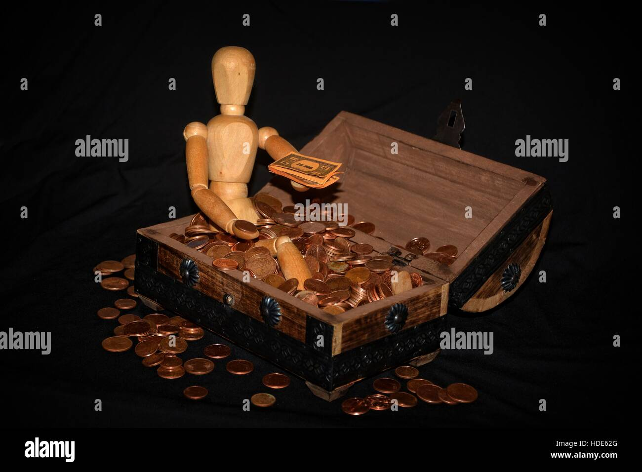Wooden figure sitting in a wooden box with money, coin and bill on the hand and with dark background - Stock Image